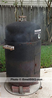 Smoke 'N Grill bullet-style smoker with mild smoke from wood chips on charcoal.